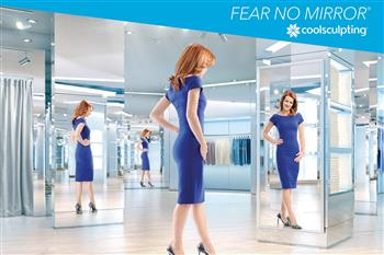 Woman in a blue dress looks at herself in the mirror
