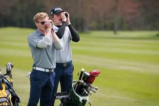 Zwei Personen mit Gucker am Golfplatz