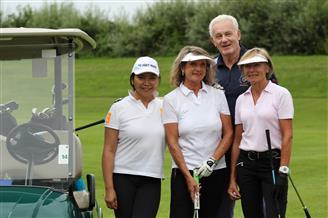 Drei Damen und ein Herr am Golfplatz