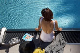 Frau sitzt am Beckenrand des Infinity Pool